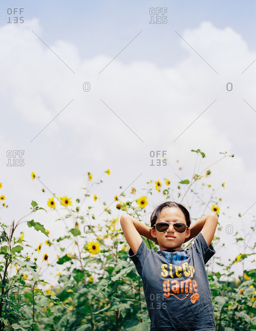 Boy with aviator sunglasses standing in a field of yellow flowers