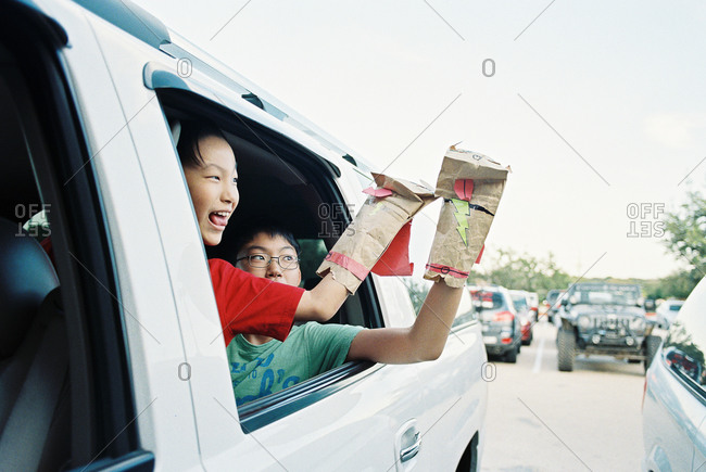 Boys hanging out of a car window playing with paper bag puppets
