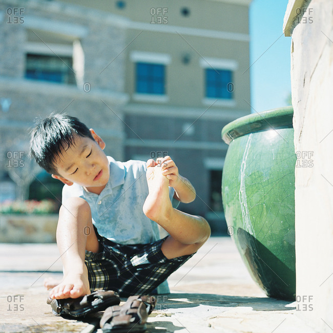 Little boy sitting on a sidewalk inspecting the soles of his feet