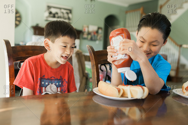 Boys sitting at a dining table putting ketchup on hot dogs