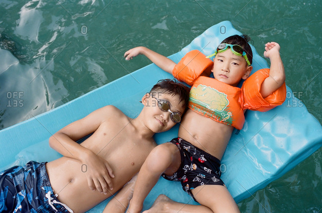 Brothers relaxing together on a pool float
