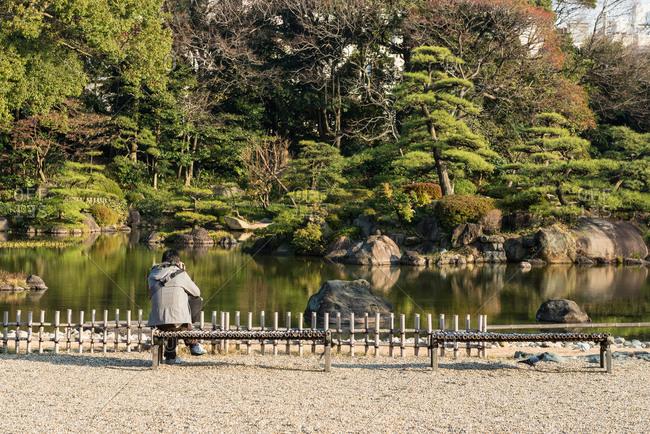 Photographer taking a photo of an island in a pond at Keitakuen Garden, Osaka, Japan