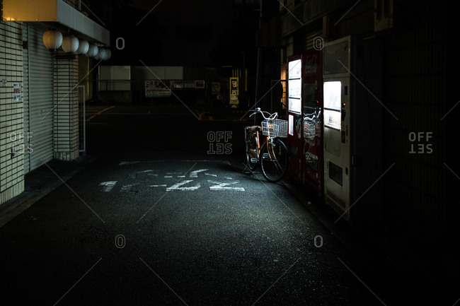 Bicycle parked next to a vending machine in an alley in Osaka, Japan