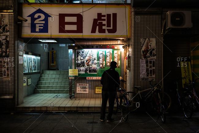 Osaka, Japan - January 16, 2016: Man standing at a cinema entrance at night in Osaka, Japan
