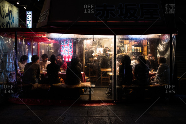 Osaka, Japan - January 16, 2016: People sitting in an outdoor dining area at a restaurant in Osaka, Japan