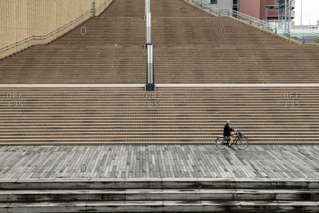 Man riding a bike in front of the steps at Minatomachi River Place in Osaka, Japan