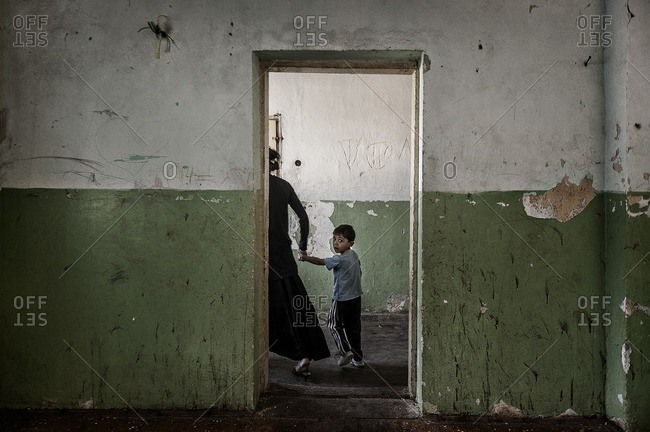 Mother and child living as refugees in former prison in Kosovo