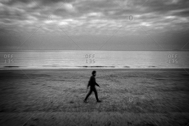 Blurred motion of man walking on beach