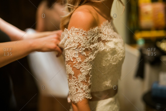Woman buttoning back of bride's gown