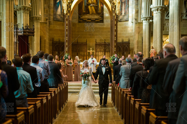 Newly married couple walking down the aisle of church