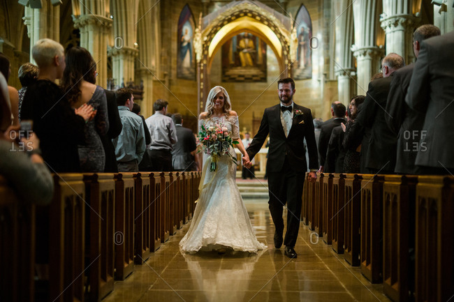 Bride and groom walk down church aisle holding hands