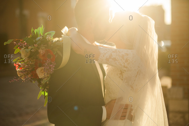 Bride and groom on sunlit street corner