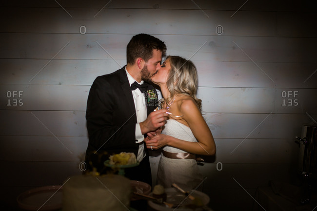 Groom and bride kiss by wedding cake