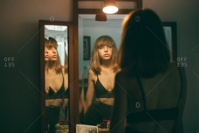 Young woman with pierced septum gazes at herself in mirror