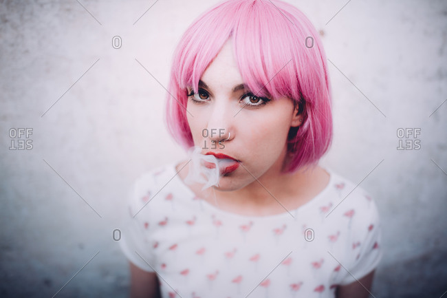 Woman in pink wig exhaling smoke from her mouth
