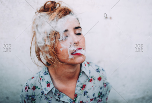Woman with nose piercings exhaling cigarette smoke with her eyes closed