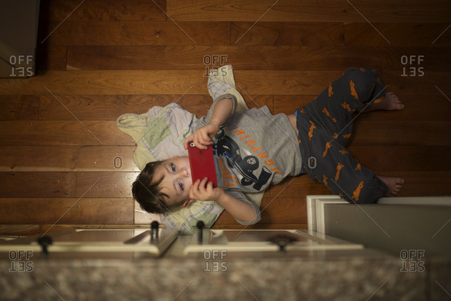 Boy lying on floor with device