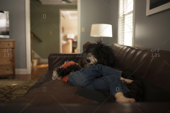 Boy cuddling dog on couch