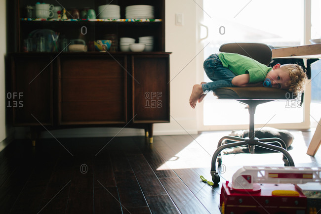 Boy with pacifier resting on wheeled chair