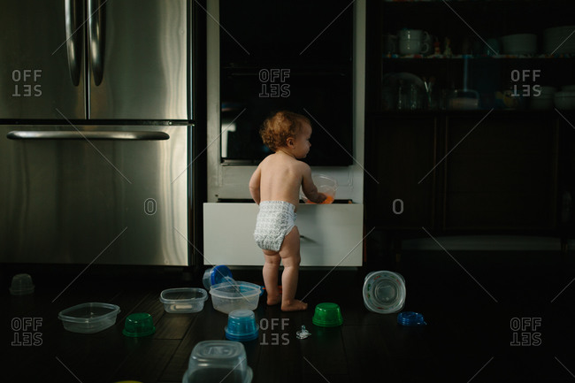 Baby in diaper playing with plastic containers on kitchen floor