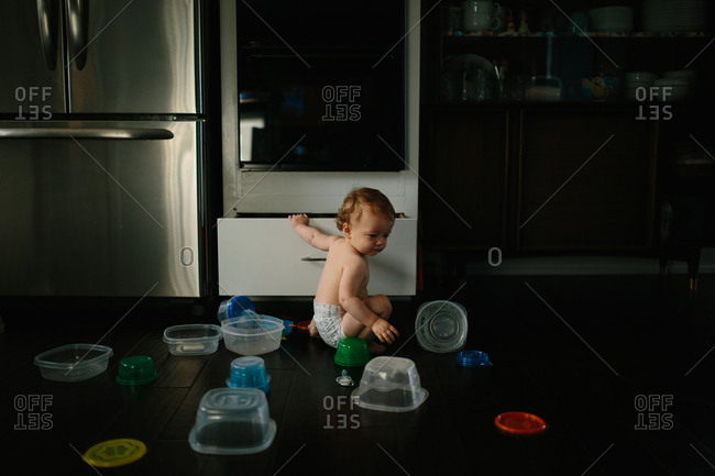 Baby in diaper pulling plastic containers out of kitchen drawer