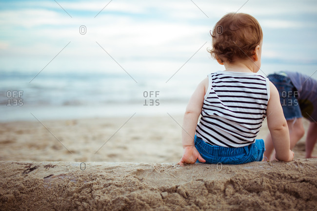 Back view of baby boy on sand-covered log at beach