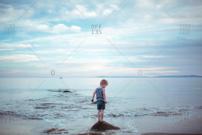 Toddler boy standing on rock at beach at dusk