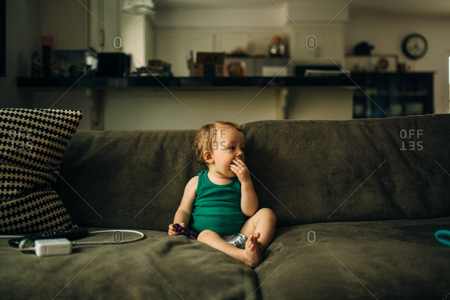 Baby boy playing with toys on couch at home