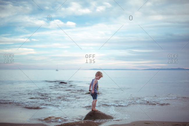 Toddler boy watches water move around rock at beach