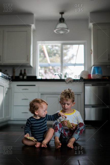 Two young brothers eat their breakfast while seated together on kitchen floor