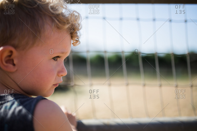 Profile portrait of toddler boy standing at fence