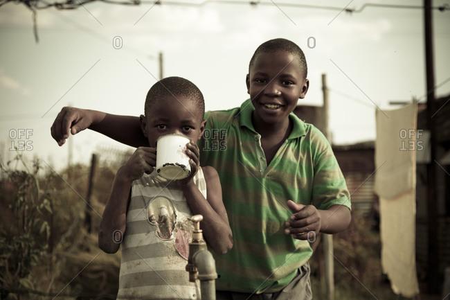 Johannesburg, Gauteng, South Africa - March 20, 2012: Young African boys by water spigot