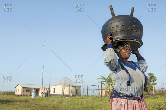 Eastern Cape, South Africa - January 19, 2011: African woman carrying cauldron