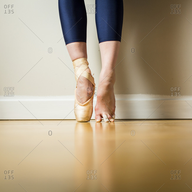 Ballerina wearing one pointe shoe standing on tip toes