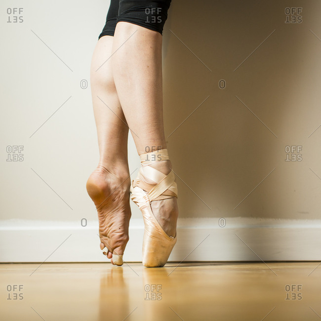 Side view of ballerina wearing one pointe shoe standing on tip toes