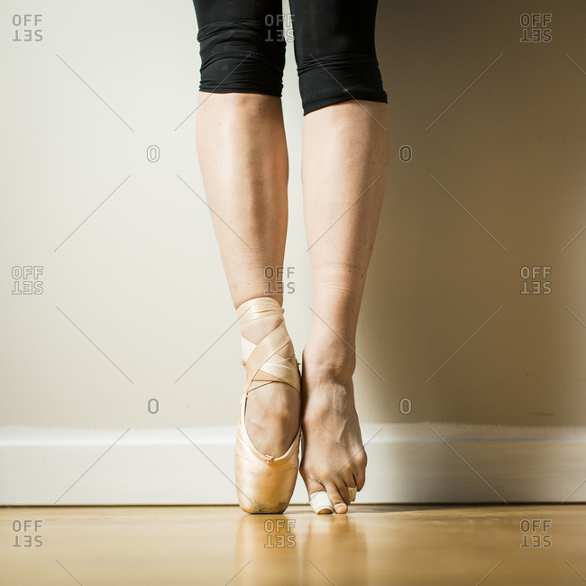 Close up of ballerina wearing one pointe shoe standing on tip toes