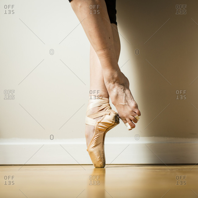 Side view of ballerina wearing pointe shoe standing on tip toes