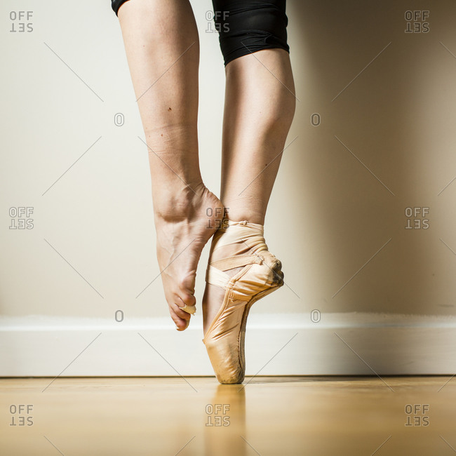 Side view of ballerina balancing on one pointe shoe
