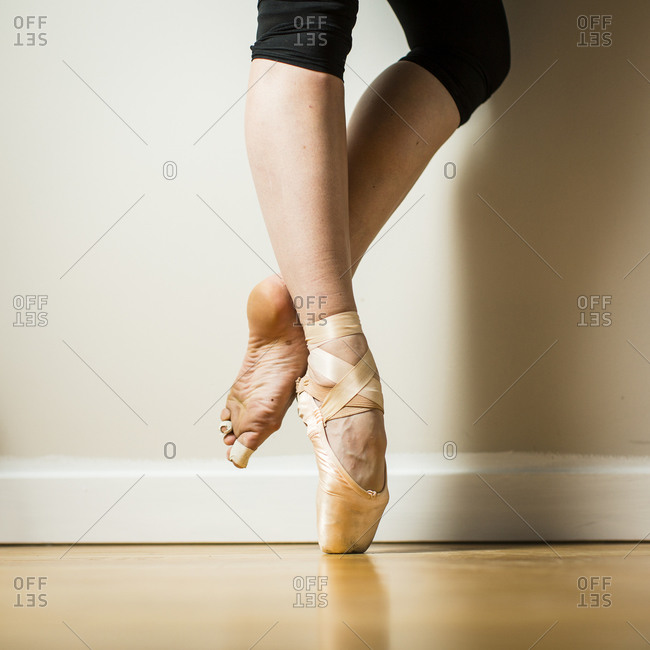 Ballerina wearing one pointe shoe crossing her ankles