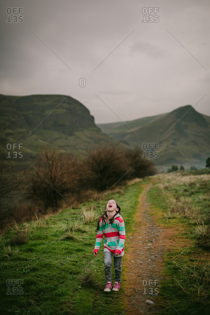 Female child holding mouth open to taste rain in field