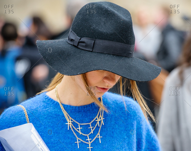 Model wearing black hat and blue knitted sweater during fashion week