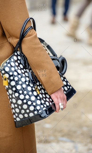Model wearing camel coat and polka dots leather bag with headphones