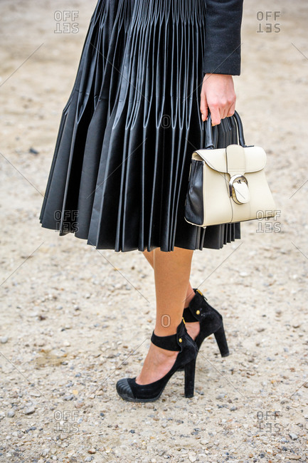 Model wearing a black leather plisse midi skirt and suede ankle strap heels