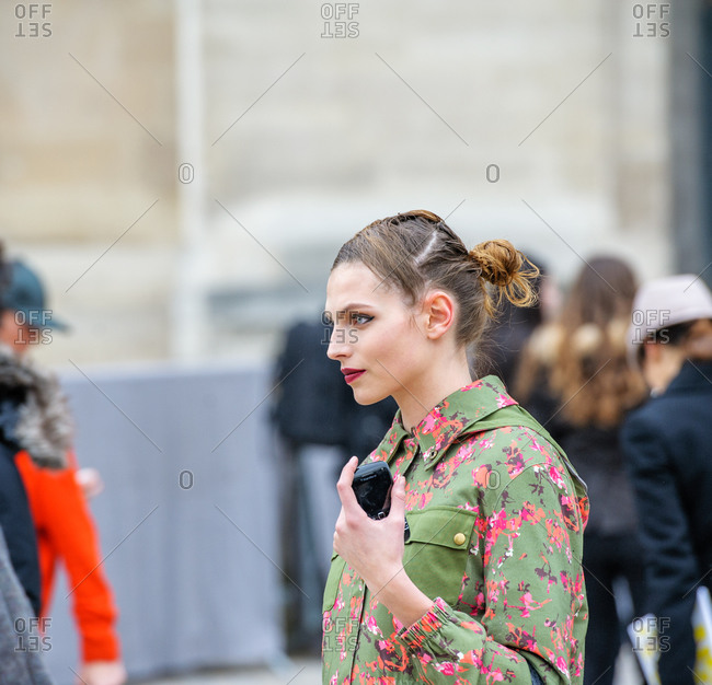 Paris, France - March 6, 2013: Model wearing a green coat with bright fuchsia floral pattern at the Paris Fashion week