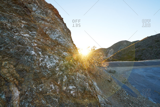 Sun rising over a rugged landscape