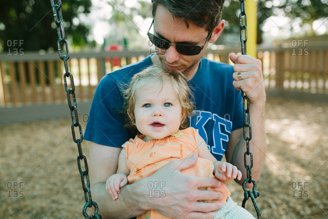 Father and daughter on a playground swingset