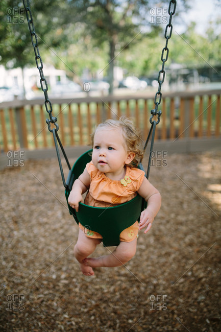 Toddler girl in a playground bucket swing