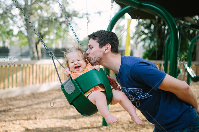 Young man kissing his daughter in a playground swing