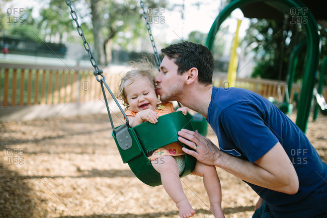 Father kissing his daughter in a swing at a playground