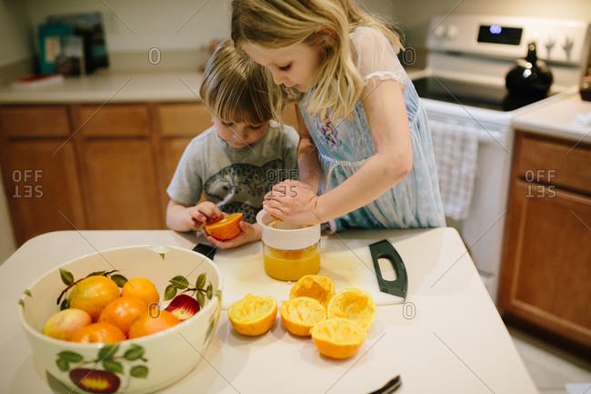 Children juicing oranges to make freshly squeezed orange juice
